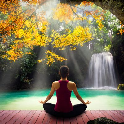 41619177 - young woman in yoga pose sitting near watefall rear view